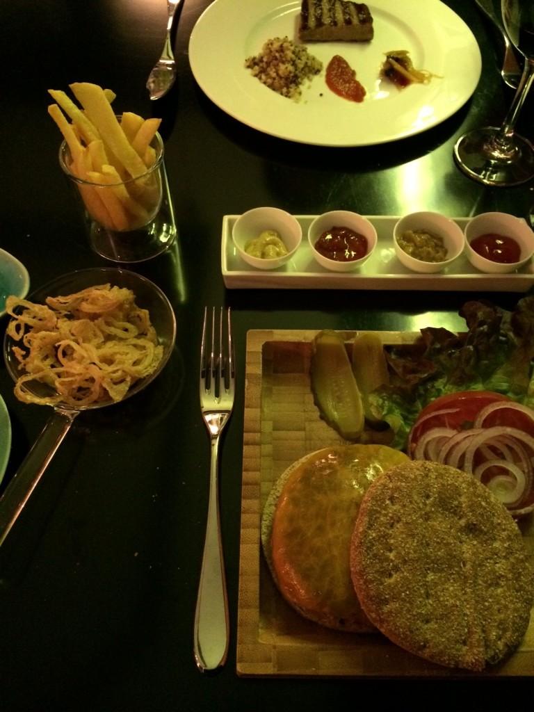 La hamburguesa de Beker6 está bañada con cerveza negra y se acompaña de aritos de cebolla, patatas fritas y exóticas salsas