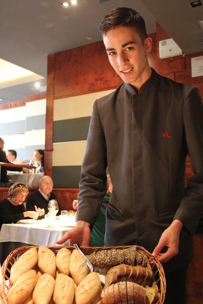 Ovaid, joven camarero, propone una selección de panes de Madre Hizo Pan entre los que destaca el de naranja y pasas ©LAGASTRONOMA