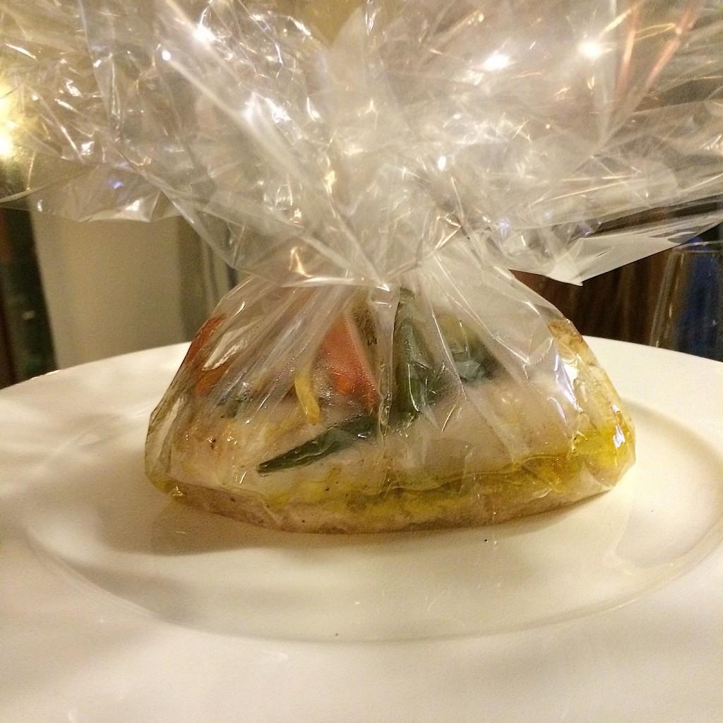 La merluza de pincho se sirve en un papel transparente el cual cortan en Ático