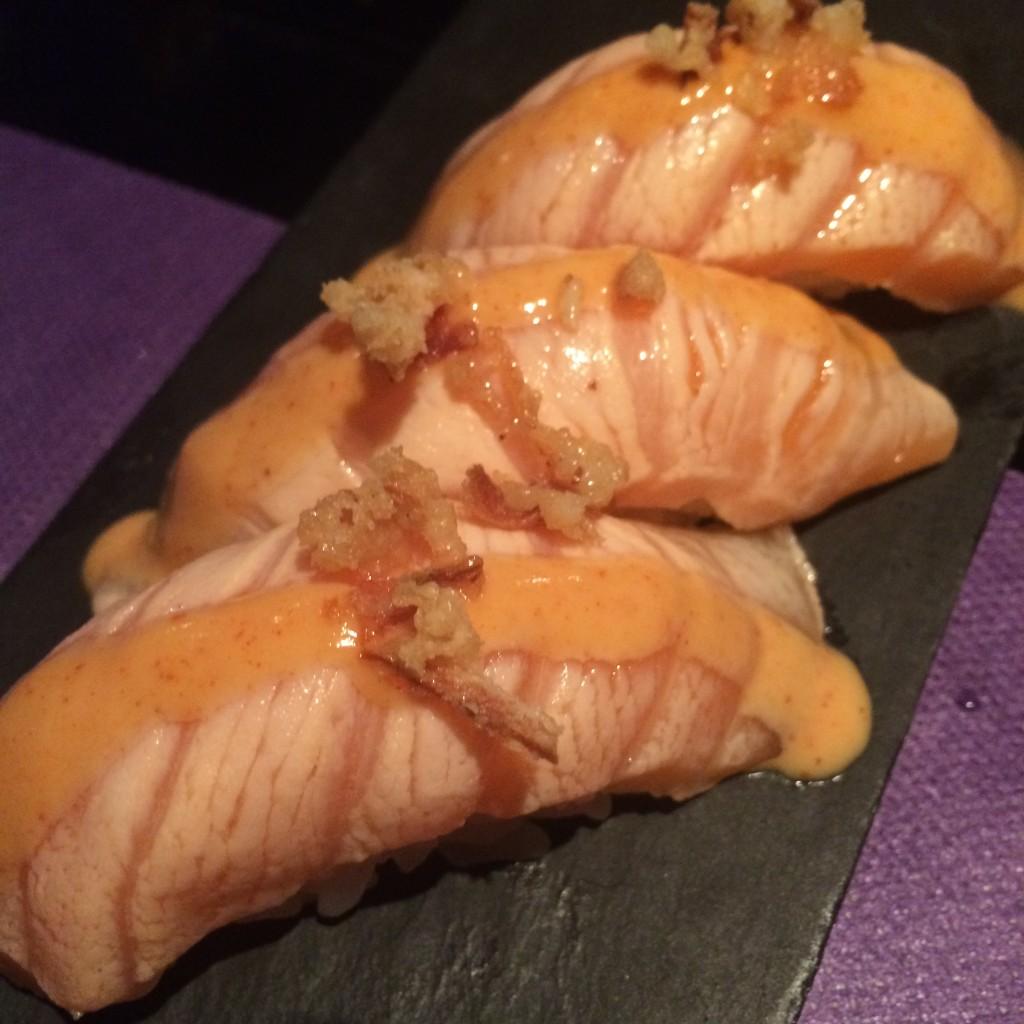 Nigiri de salmón flambeado con salsa tiger y virutas de cebolla frita. SKYSUSHI