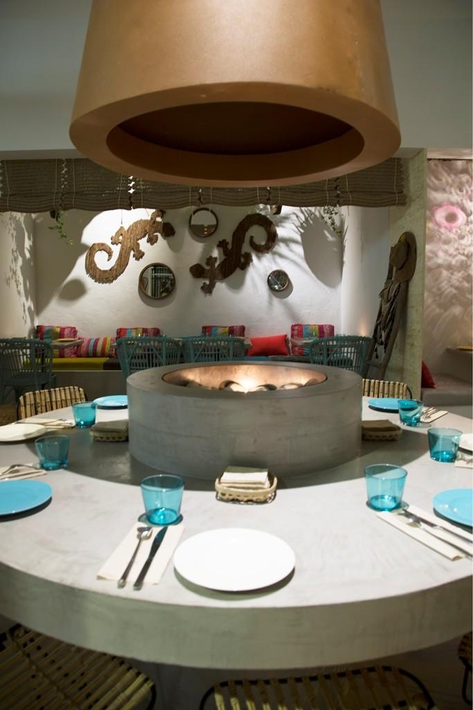 En el corazón del espacio nos encontramos con una chimenea integrada en una mesa circular para 8 comensales, donde poder comer alrededor del fuego