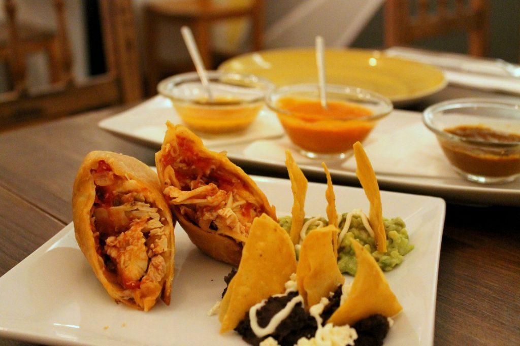 Chimichanga de tinga de pollo con guacamole, frijoles refritos y totopos, el Queso de cabra a la plancha con miel y tomillo. Meridiano 100