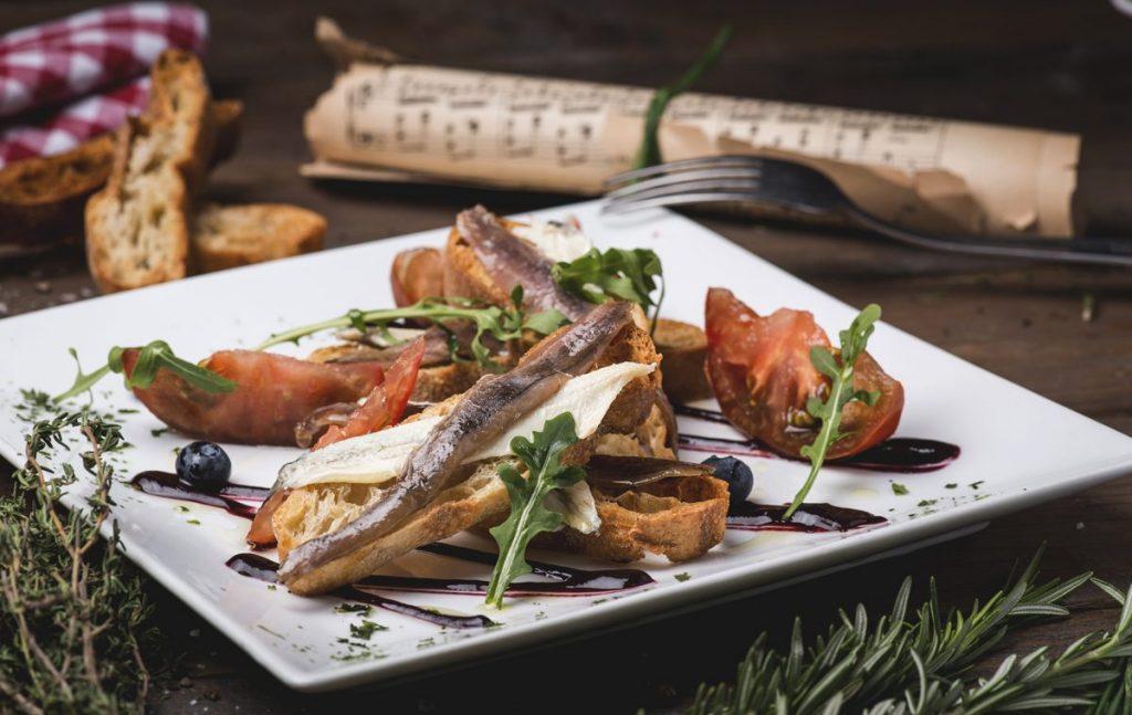 Matrimonio de anchoas y boquerones en pan de cristal con gajo oriental de tomate. LaLina Gastrobar