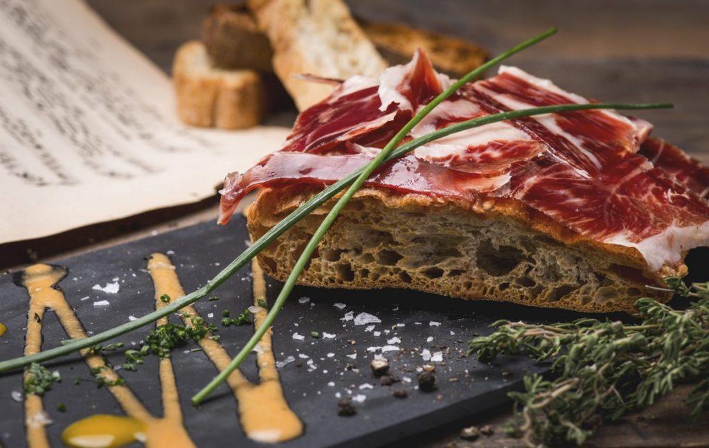 Tosta en pan de cristal de Cecina de León con base de mermelada de pimientos rojos, de Jamón ibérico y/o de queso de tetilla con base de tomate natural. LaLina Gastrobar